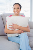 Relaxed woman sitting on sofa holding pillow