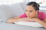 Side view of thoughtful woman lying on the sofa
