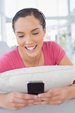 Smiling woman lying on sofa and texting