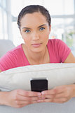 Serious woman lying on sofa and texting