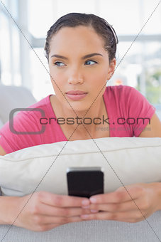 Thoughtful woman lying on sofa and texting