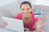 Pretty woman holding laptop showing credit card