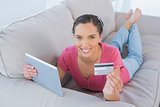 Casual woman lying with a credit card and a tablet