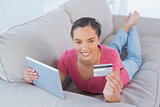 Woman doing online shopping with tablet and credit card