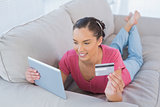 Attractive woman making an online payment with her credit card while lying on a sofa