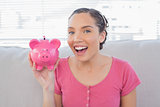 Happy woman showing piggy bank while sitting on sofa