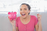Smiling woman sitting on sofa and holding piggy bank