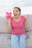 Happy woman sitting on sofa showing piggy bank