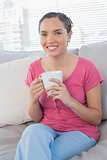 Relaxed woman sitting on sofa holding mug of coffee