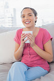 Smiling woman sitting on sofa holding mug of coffee
