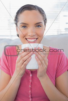 Portrait of smiling woman holding a cup of coffee