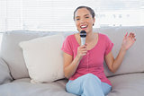 Brunette sitting on her sofa singing into microphone looking at camera
