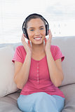 Calmful woman listening to music on sofa