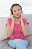Relaxed woman listening to music on sofa