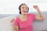 Dancing woman sitting on sofa listening to music