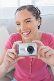 Cheerful woman in living room taking pictures