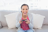 Smiling woman sitting on sofa playing video games