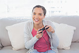 Happy woman sitting on sofa playing video games