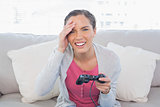 Irritated pretty woman sitting on sofa playing video games