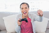 Woman playing video games on sofa and winning