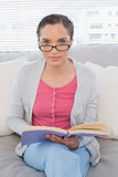 Relaxed woman sitting on sofa holding a book