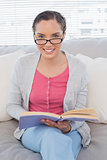 Smiling woman wearing reading glasses sitting on sofa holding a book