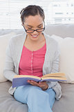 Smart woman with reading glasses sitting on sofa and reading a book