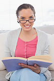 Smiling woman with reading glasses sitting on sofa and holding a book