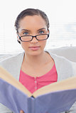 Serious woman with reading glasses holding a book