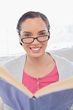 Smiling woman with reading glasses holding a book
