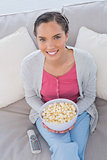 High angle view of woman sitting on sofa holding popcorn