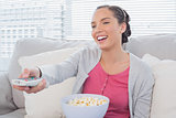 Cheerful attractive woman eating popcorn while watching tv