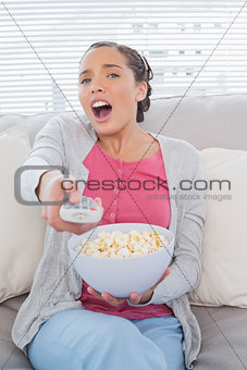 Astonished attractive woman eating popcorn while watching tv