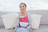 Smiling attractive woman eating popcorn while watching tv