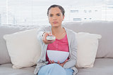 Unsmiling woman sitting on sofa wathing televion and holding popcorn
