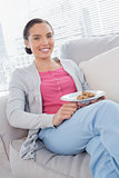 Cheerful woman sitting on sofa holding plate of cookies