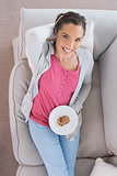 Relaxed woman lying on sofa and holding plate of cookies