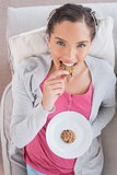 Smiling woman lying on sofa eating cookie