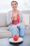 Cheerful woman sitting on sofa holding orange juice