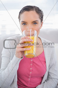 Attractive woman sitting on sofa drinking orange juice