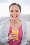 Smiling woman sitting on sofa and holding orange juice