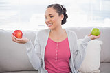 Cheerful woman sitting on sofa holding green and red apple looking at the red one