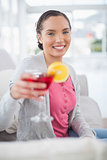 Smiling woman sitting on sofa and showing cocktail
