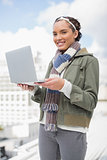 Happy woman standing outside and holding laptop
