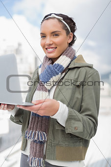 Attractive woman standing outside and holding laptop