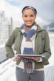 Portait of smiling woman standing outside and holding laptop