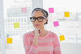 Thoughtful woman with glasses in creative office
