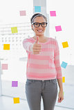Smiling woman standing in her creative office giving thumb up