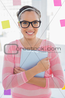 Smiling artist with glasses holding tablet and looking at camera