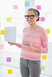 Smiling artist with glasses using laptop